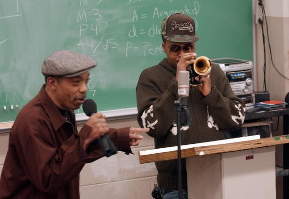 Nas (R) plays trumpet as his musician father Olu Dara talks to students in Melvin M. Jones'  improvisational jazz class at Morehouse College on January 24, 2005, in Atlanta, Georgia.